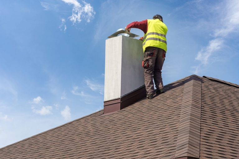 Roofer working on chimney repair in Denton county.