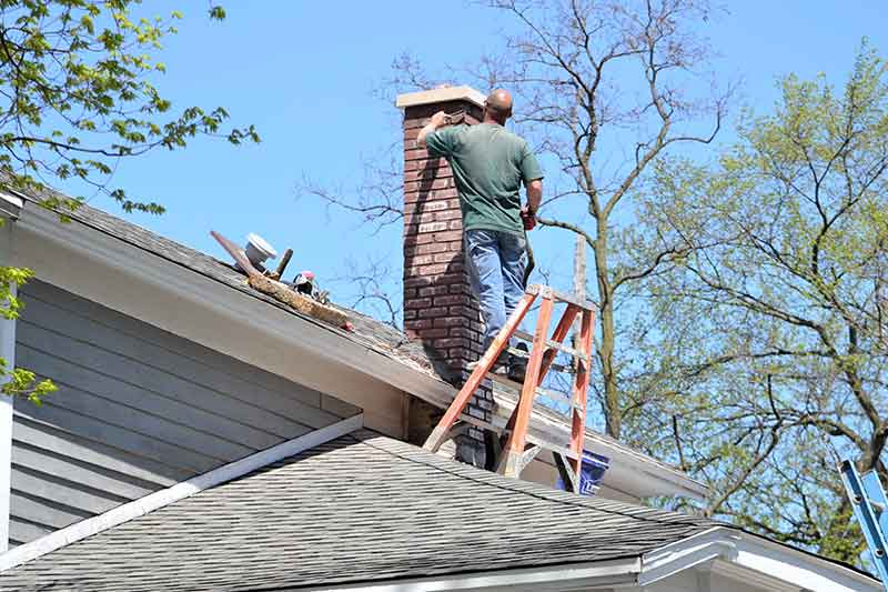 Roofer repairing chimney.