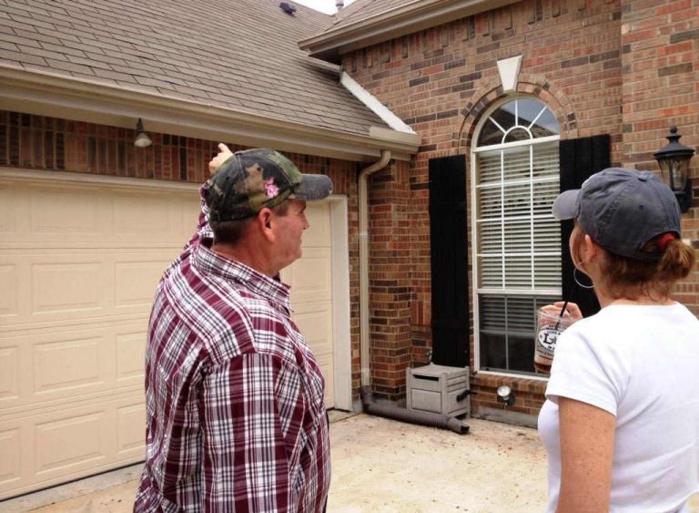 Owner of DKG Roofing pointing to Denton County homeowner's roof.