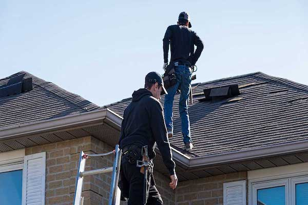 Denton County roof inspectors climbing on residential roof.