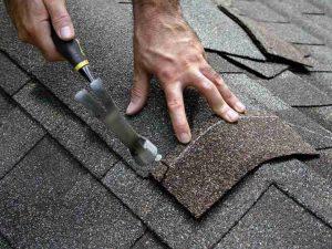 Denton County homeowner performing minor roof repair by replacing an asphalt shingle.