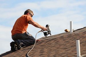 Homeowner doing their own roof repair instead of working with roofing companies.