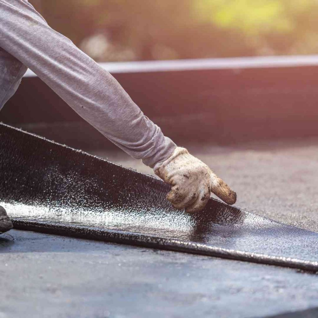 Roofing tar being applied to a residential roof
